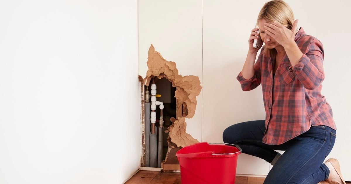Woman cleaning up a burst pipe